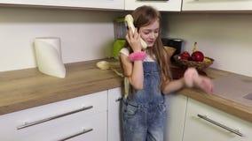 Μικρό κορίτσι που μιλά στο αναδρομικό τηλέφωνο στην κουζίνα απόθεμα βίντεο