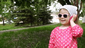 Μικρό κορίτσι που μιλά σε ένα τηλέφωνο παιδιών ` s στο πάρκο φιλμ μικρού μήκους