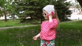 Μικρό κορίτσι που μιλά σε ένα τηλέφωνο παιδιών ` s στο πάρκο απόθεμα βίντεο
