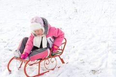 Μικρό κορίτσι που οδηγά ένα έλκηθρο στο χιόνι Στοκ εικόνες με δικαίωμα ελεύθερης χρήσης
