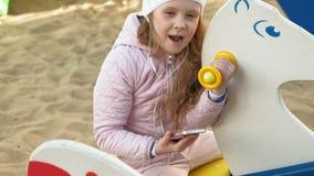 Μικρό κορίτσι που οδηγά μια ταλάντευση και που χρησιμοποιεί ένα τηλέφωνο με τα ακουστικά φιλμ μικρού μήκους