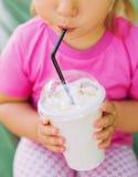 Μικρό κορίτσι που πίνει milkshake μέσω ενός αχύρου Στοκ Φωτογραφία