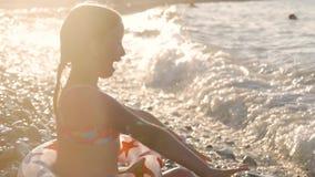 Μικρό κορίτσι που παίζει ευτυχώς με τα κύματα στην παραλία απόθεμα βίντεο