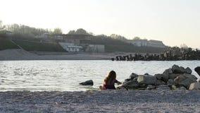 Μικρό κορίτσι που παίζει την κοντινή θάλασσα απόθεμα βίντεο