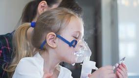 Μικρό κορίτσι που παίρνει την εισπνοή αερολυμάτων με Mom απόθεμα βίντεο