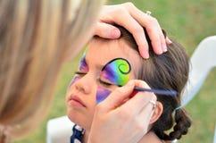 Μικρό κορίτσι που παίρνει το πρόσωπό της χρωματισμένο Στοκ Εικόνες