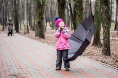 Μικρό κορίτσι που περπατά κάτω από την ομπρέλα σε ένα πάρκο στοκ φωτογραφία με δικαίωμα ελεύθερης χρήσης