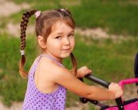 Μικρό κορίτσι που περπατά με έναν περιπατητή παιχνιδιών. Στοκ Φωτογραφία