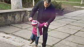 Μικρό κορίτσι που περπατά στα σκαλοπάτια μαζί με τον παππού της στο πάρκο και το χαμόγελο πόλεων οικογενειακά καρύδια έννοιας σύν απόθεμα βίντεο
