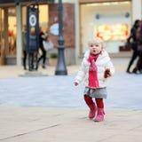 Μικρό κορίτσι που περπατά στην οδό αγορών Στοκ Φωτογραφίες