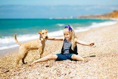 Μικρό κορίτσι που περπατά στην παραλία με ένα τεριέ κουταβιών Στοκ Φωτογραφία