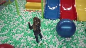 Μικρό κορίτσι που περπατά στις μικρές σφαίρες στο κέντρο παιχνιδιού των παιδιών φιλμ μικρού μήκους