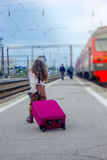 Μικρό κορίτσι που πηγαίνει να εκπαιδεύσει - ταξίδι με την τσάντα στο σιδηροδρομικό σταθμό Στοκ Εικόνες