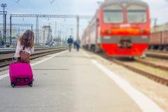 Μικρό κορίτσι που πηγαίνει να εκπαιδεύσει - ταξίδι με την τσάντα στο σιδηροδρομικό σταθμό Στοκ φωτογραφία με δικαίωμα ελεύθερης χρήσης
