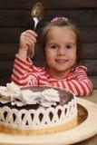 Μικρό κορίτσι που πηγαίνει να φάει το κέικ σοκολάτας Στοκ Φωτογραφία