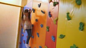 Μικρό κορίτσι που πηδά με έναν τοίχο αναρρίχησης στη λίμνη με τους μαλακούς κύβους σε ένα κέντρο τραμπολίνων φιλμ μικρού μήκους