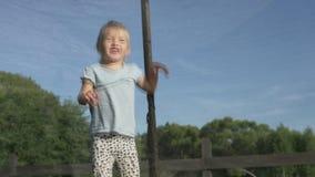 Μικρό κορίτσι που πηδά σε ένα τραμπολίνο το καλοκαίρι έξω απόθεμα βίντεο
