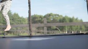 Μικρό κορίτσι που πηδά σε ένα τραμπολίνο το καλοκαίρι στο ναυπηγείο φιλμ μικρού μήκους