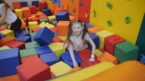 Μικρό κορίτσι που πηδά στη λίμνη με τους ζωηρόχρωμους μαλακούς κύβους σε ένα κέντρο ψυχαγωγίας τραμπολίνων απόθεμα βίντεο