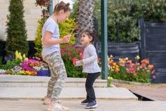 Μικρό κορίτσι που πηδά, χορεύοντας, έχοντας τη διασκέδαση υπαίθρια Ευτυχείς θερινές διακοπές στοκ φωτογραφίες