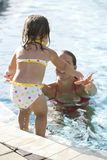Μικρό κορίτσι που πηδά στη μητέρα στην πισίνα Στοκ φωτογραφία με δικαίωμα ελεύθερης χρήσης