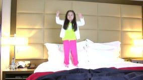 Μικρό κορίτσι που πηδά στο κρεβάτι απόθεμα βίντεο