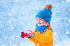 Μικρό κορίτσι που πιάνει τις νιφάδες χιονιού Στοκ Φωτογραφία