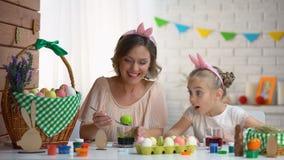 Μικρό κορίτσι που προσέχει αναστατωμένα το βυθίζοντας αυγό μητέρων στον πράσινο χρωματισμό τροφίμων, Πάσχα απόθεμα βίντεο