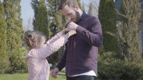 Μικρό κορίτσι που προσπαθεί να κουμπώσει το πουκάμισο του πατέρα που στέκεται υπαίθρια Οικογενειακός ελεύθερος χρόνος υπαίθρια, ά φιλμ μικρού μήκους