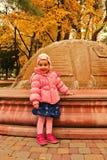 Μικρό κορίτσι που στέκεται κοντά στην πηγή το φθινόπωρο Στοκ Εικόνα