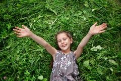 Μικρό κορίτσι που στηρίζεται στην πράσινη χλόη Στοκ φωτογραφία με δικαίωμα ελεύθερης χρήσης