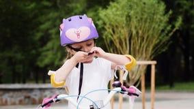 Μικρό κορίτσι που τίθεται στο προστατευτικούς κράνος και το γύρο ποδηλάτων στο ποδήλατο απόθεμα βίντεο