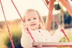 Μικρό κορίτσι που ταλαντεύεται σε μια παιδική χαρά Παιδική ηλικία, ευτυχής, θερινή υπαίθρια έννοια Στοκ Φωτογραφία