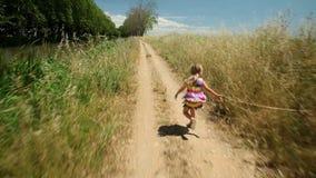 Μικρό κορίτσι που τρέχει κατά μήκος της διαδρομής πορειών στη φύση απόθεμα βίντεο
