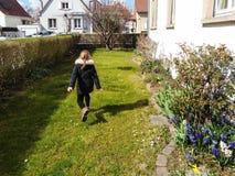 Μικρό κορίτσι που τρέχει στον ανθίζοντας κήπο, χρόνος άνοιξη στοκ φωτογραφία με δικαίωμα ελεύθερης χρήσης