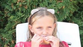 Μικρό κορίτσι που τρώει ένα σάντουιτς στη φύση απόθεμα βίντεο