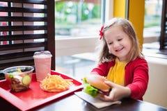 Μικρό κορίτσι που τρώει ένα χάμπουργκερ στο εστιατόριο γρήγορου φαγητού στοκ εικόνες με δικαίωμα ελεύθερης χρήσης