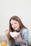 Μικρό κορίτσι που τρώει τα δημητριακά στο πρόγευμα Στοκ Φωτογραφία