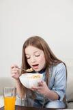 Μικρό κορίτσι που τρώει τα δημητριακά στο πρόγευμα Στοκ φωτογραφία με δικαίωμα ελεύθερης χρήσης