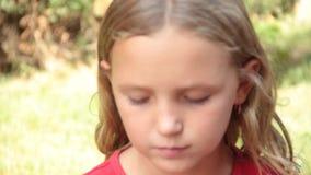 Μικρό κορίτσι που τρώει τη σοκολάτα στη φύση φιλμ μικρού μήκους