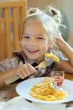 Μικρό κορίτσι που τρώει τις τηγανιτές πατάτες στοκ εικόνες