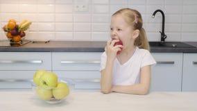 Μικρό κορίτσι που τρώει το μήλο στην κουζίνα φιλμ μικρού μήκους