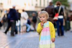Μικρό κορίτσι που τρώει το παγωτό που περπατά στην πόλη Στοκ φωτογραφίες με δικαίωμα ελεύθερης χρήσης