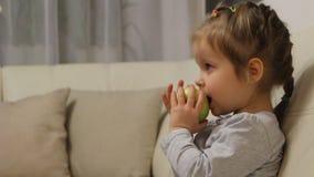 Μικρό κορίτσι που τρώει το πράσινο μήλο προσέχοντας τη TV απόθεμα βίντεο