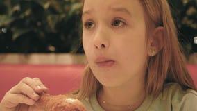 Μικρό κορίτσι που τρώει το τηγανισμένο κοτόπουλο στον καφέ απόθεμα βίντεο