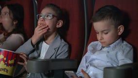 Μικρό κορίτσι που τρώει popcorn στη κινηματογραφική αίθουσα Αγόρι που χρησιμοποιεί το smartphone στον κινηματογράφο φιλμ μικρού μήκους