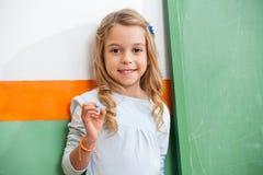 Μικρό κορίτσι που υπερασπίζεται τον πράσινο πίνακα κιμωλίας μέσα στοκ φωτογραφία