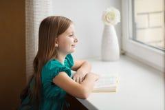 Μικρό κορίτσι που φαίνεται έξω το παράθυρο στοκ εικόνες