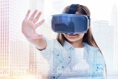 Μικρό κορίτσι που φορά την κάσκα VR και που αντέχει το φοίνικά της Στοκ Εικόνες
