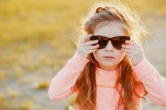 Μικρό κορίτσι που φορά υπαίθρια τα γυαλιά ηλίου Στοκ φωτογραφία με δικαίωμα ελεύθερης χρήσης